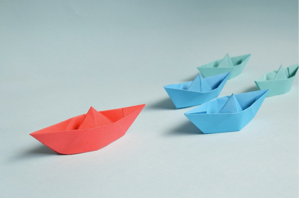 Origami paper boats in a formation with one as the leader